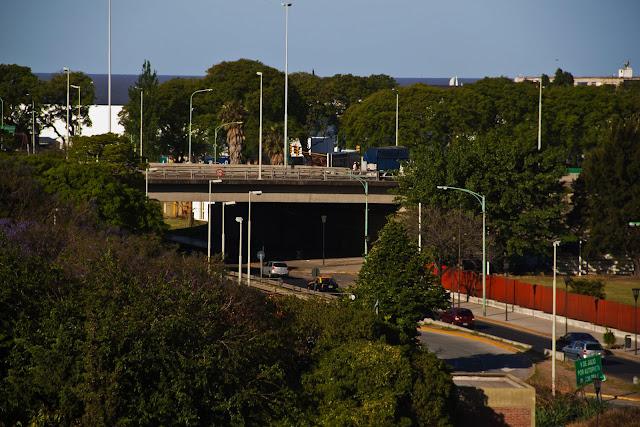 Autos circulando por calle con puente aéreo