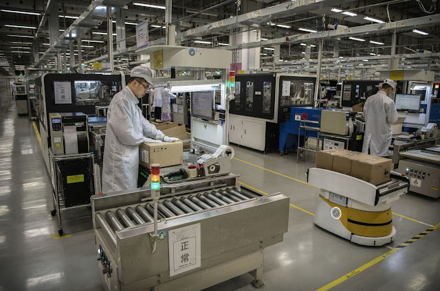 A worker packs up new smartphone devices at the end of the production line