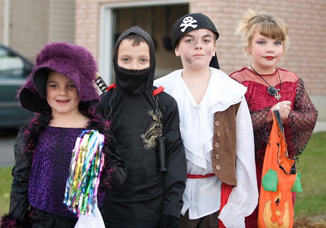 Four kids dressed up and ready for trick or treating on Halloween.