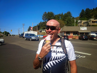 A cyclist enjoying an ice cream in the sun shine.