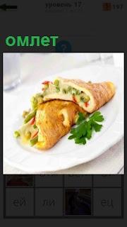 На тарелке приготовлена еда омлет и зеленью украшено само блюдо