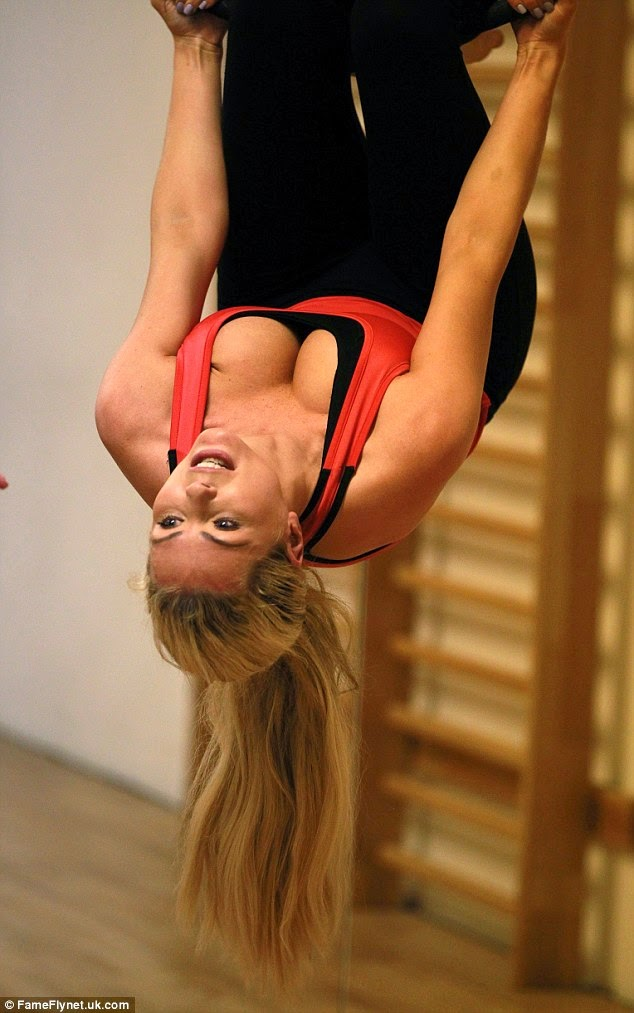 busty celebrity Nicola McLean hangs in a precarious upside down position