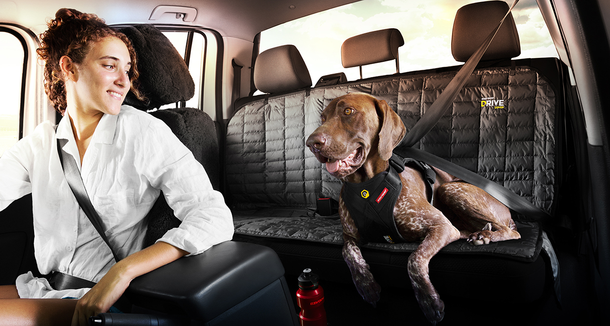 Woman smiles at her dog wearing an EzyDog Drive Car Harness  lying on EzyDog Drive Seat Cover