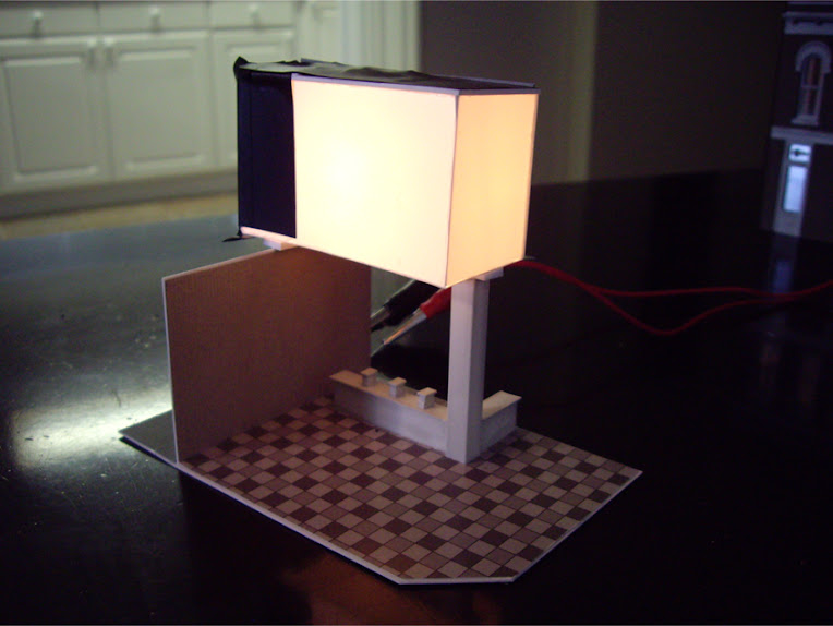 Removable interior scene depicting a bank with a styrene light diffuser attached on top for Other Corner Café kit