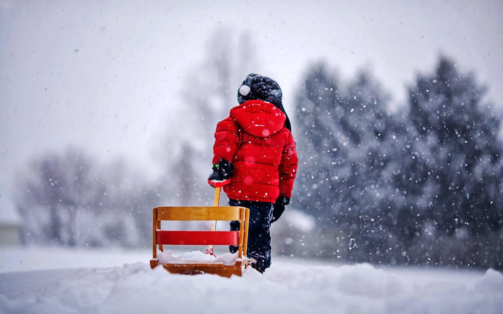Jongen met slee in de sneeuw