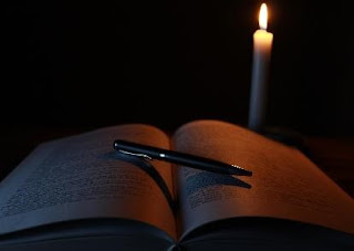 Book with a pen across the open pages, with a candle in the background