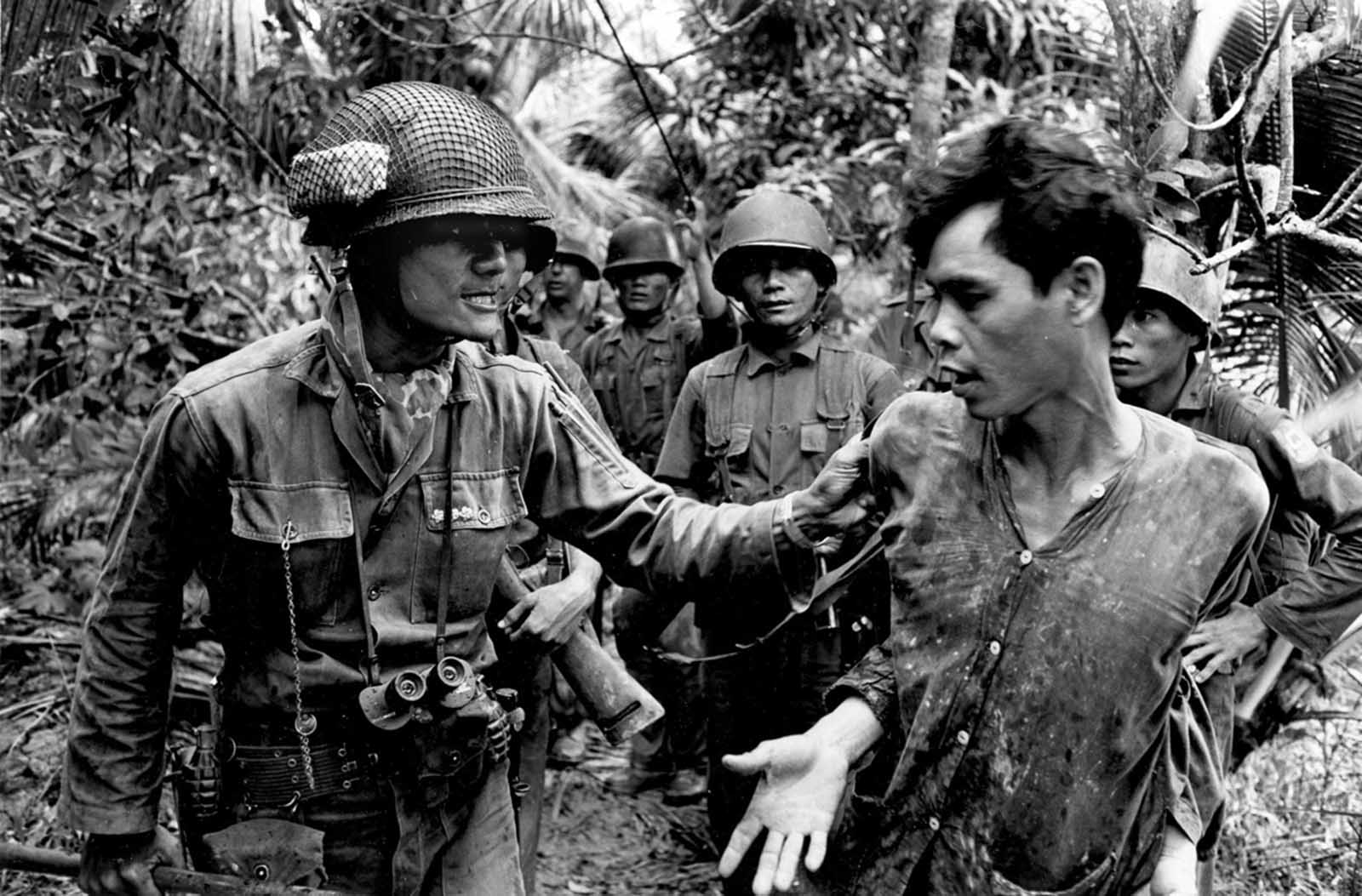 A Vietnamese battalion commander, Captain Thach Quyen, left, interrogates a captured Viet Cong suspect on Tan Dinh Island, Mekong Delta, in 1965.