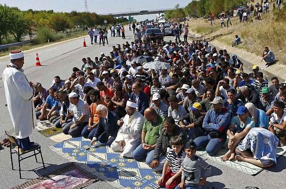 Imigrantes islâmicos praticando seu culto numa estrada da Eslovênia