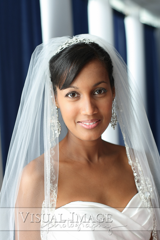Bride with long flowing veil in natural light of window at Discovery World