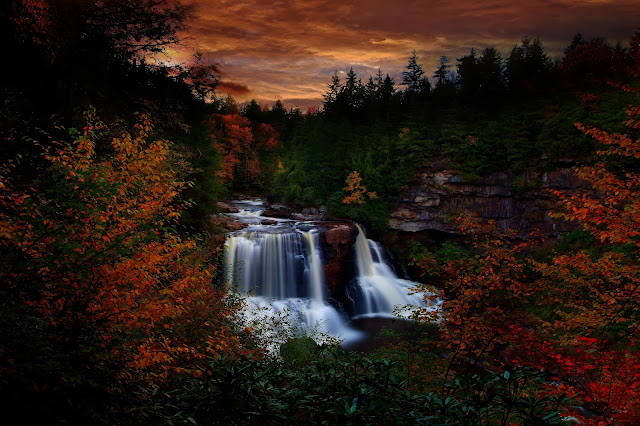 Autumn Foliage surrounds these beautiful waterfalls during a fall evening sunset sky. Blackwater falls are some of the most beautiful waterfalls in all of West Virginia. the river is known and named for the dark colored water stained from minerals in the river sediment.