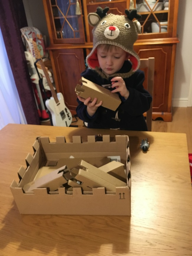 boy-playing-with-tower-of-cardboard-castle
