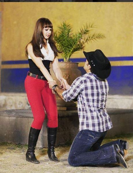 Ivana com blusa branca e preta sem mangas, cinto preto e calça vermelha colada, de pé há um homem de joelhos segurando suas mãos, implorando