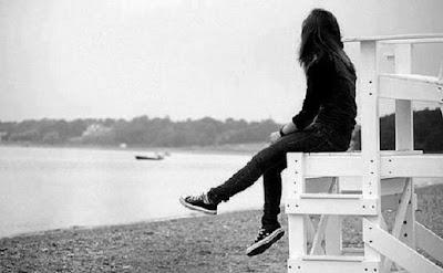una joven adolescente sentada sola frente a un rio