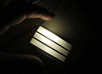 Modern dolls' house miniature light box, half built but lit up, with hand for size reference.