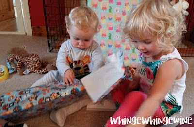 The big toddler helping the birthday boy to open his presents