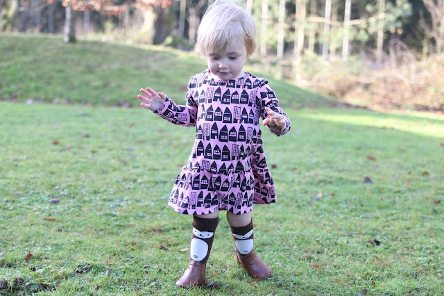 pink dress for toddler girl with black houses print from me&i teamed with knee high brown monkey socks and brown ankle boots from primark