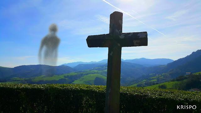 cruz de cementerio y un fantasma con el fondo de montes