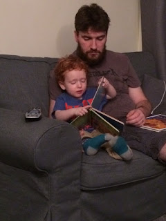 Little boy, sitting with his Daddy, reading the book