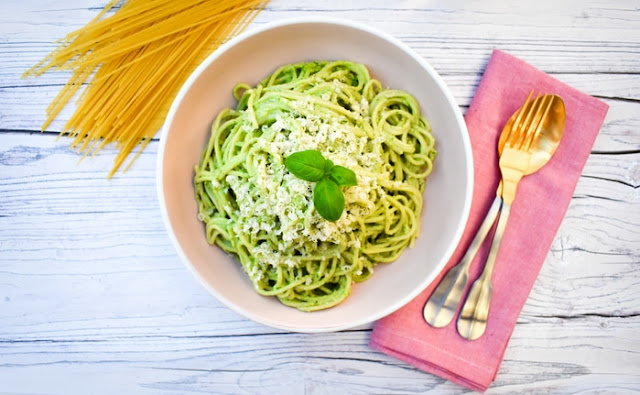 Kale & Cashew Pesto Spaghetti in a pale pink bowl topped with grated parmesan