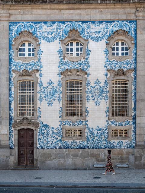 Mujer caminando delante de una fachada de azulejos en Oporto