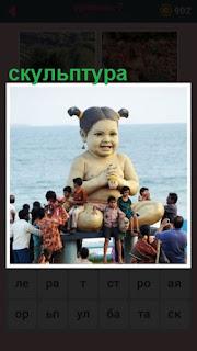 на берегу сделана скульптура девочка и посетители вокруг