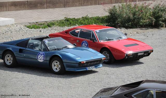 Roter Ferrari 308 GT4 und blauer Ferrari 308 GTS stehen nebeneinander auf Parkplatz vor dem Kulm Country Club, Passione Engadina Event