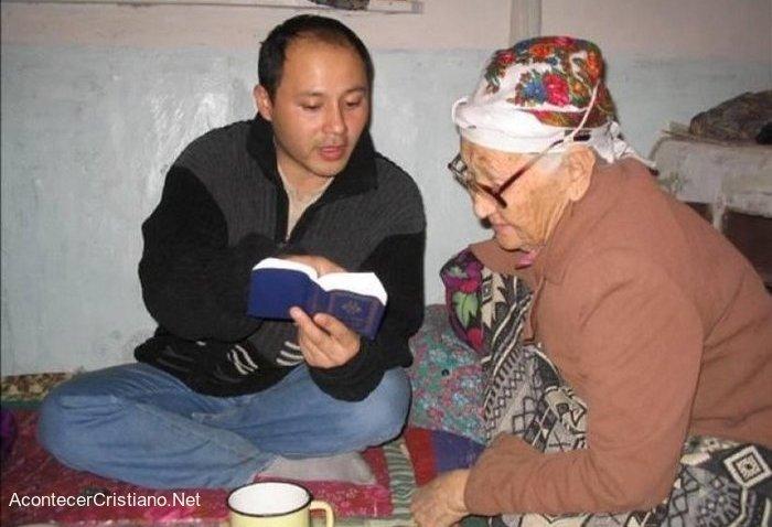 Hombre cristiano enseñando la Biblia a una anciana
