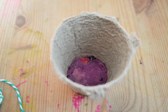 A grey plant pot with playdough in the bottom.