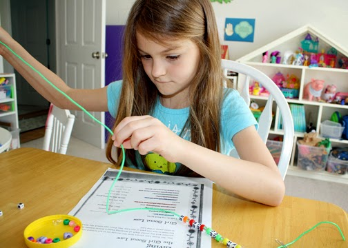 Tessa laced appropriately colored pony beads and alphabet beads onto plastic cord to represent the various lines of the Girl Scout Law. Afterward, we fashioned the cord into a necklace to help her memorize the Law.