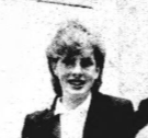 Black and white image of the head and shoulders of a smiling woman in smart formal dress
