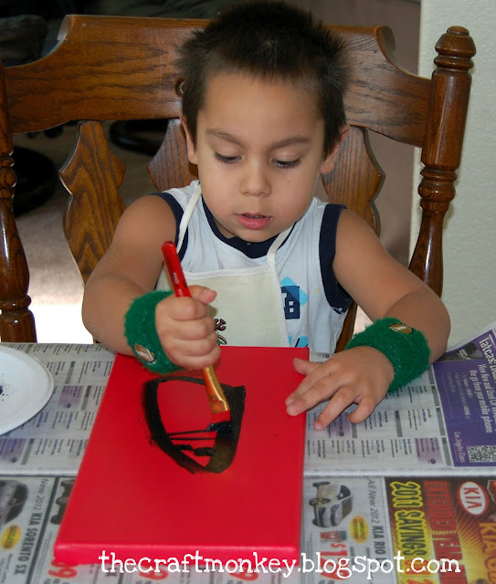 Little boy painting a canvas