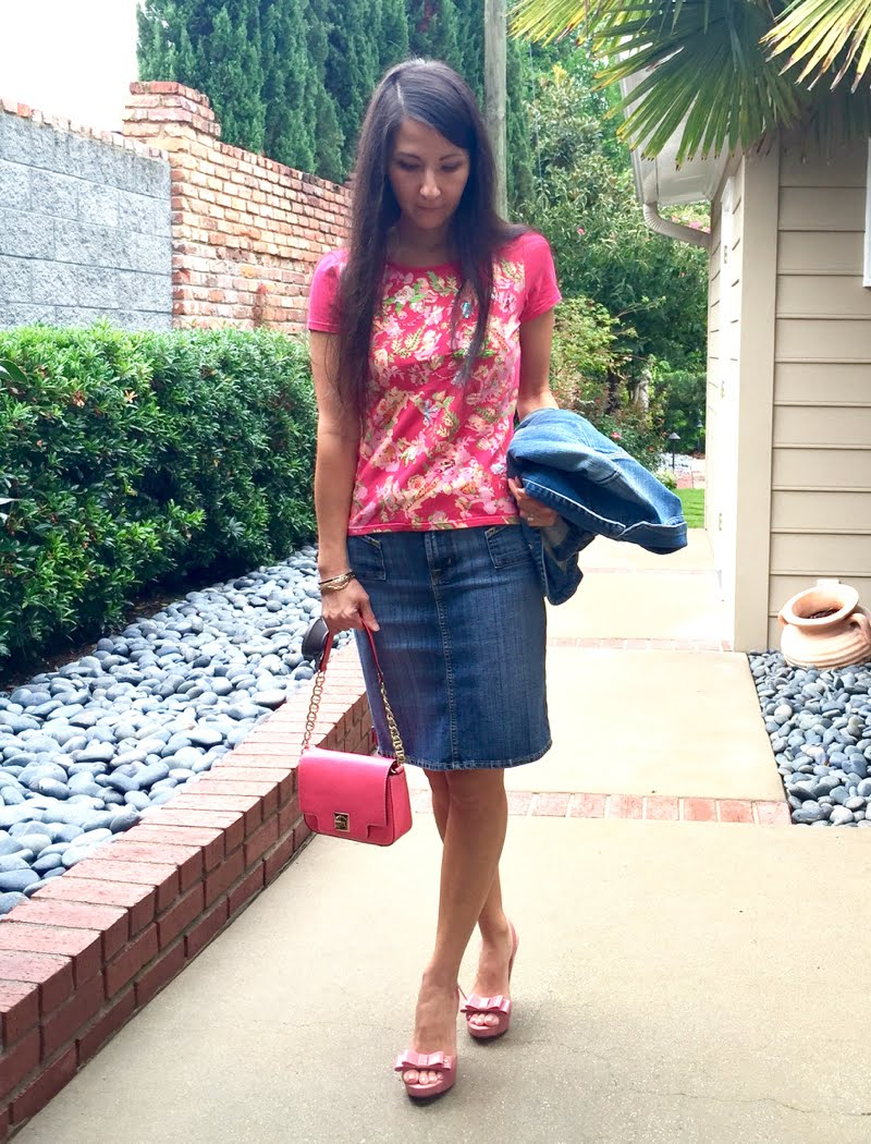 Wearing patterned pink T shirt with jean skirt. Holding jean jacket and pink small bag and wearing pink sandals with bows.