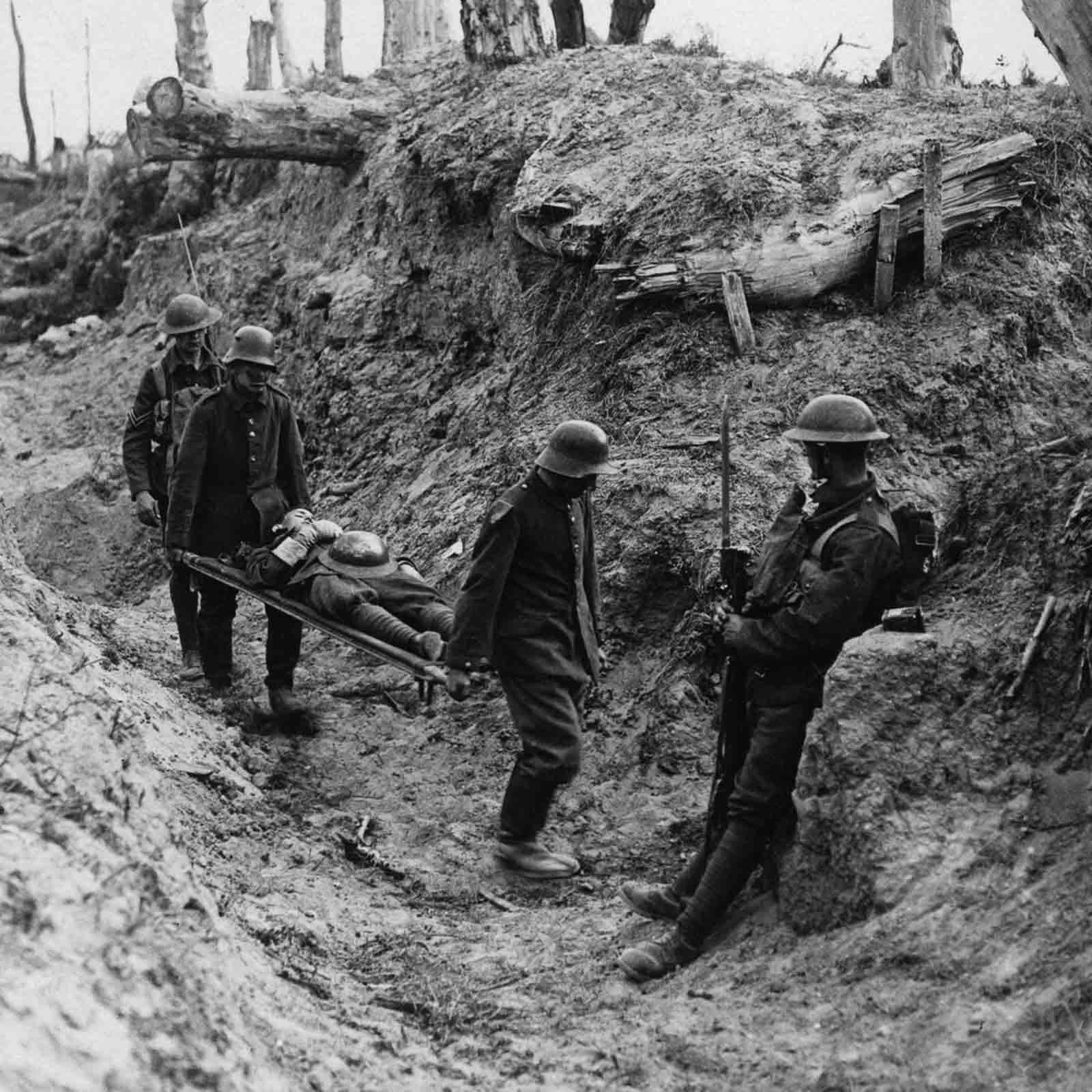 Prisioneros alemanes llevan heridos británicos durante el asalto a Trones Wood.