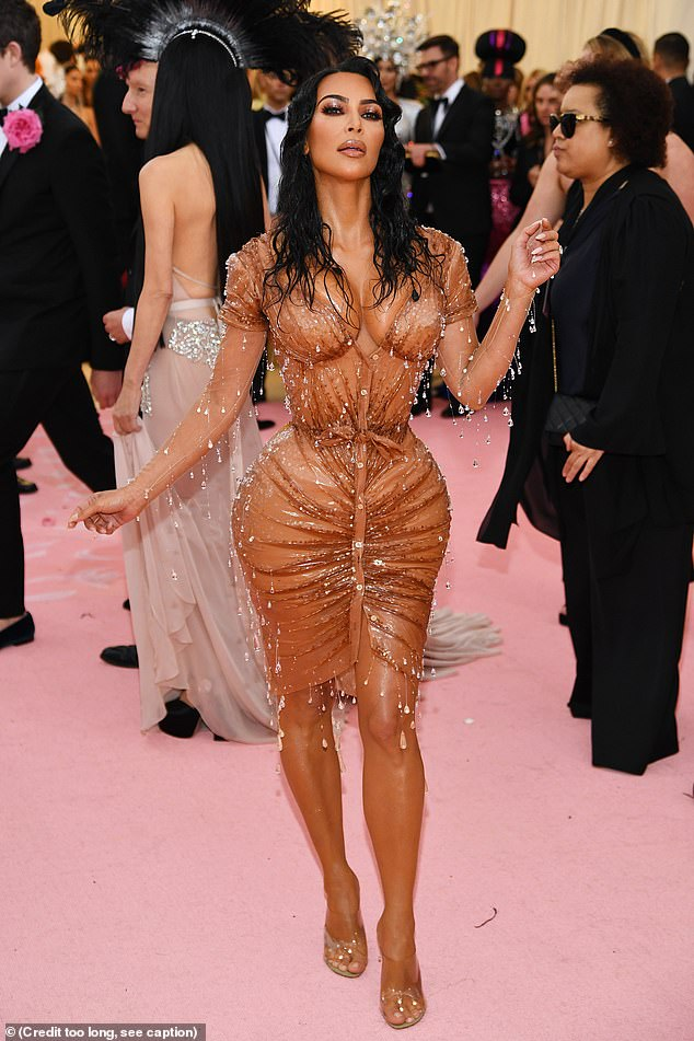 Kim Kardashian arrives at the 2019 Met Gala in a stunning caramel coloured gown that accentuates her hourglass figure