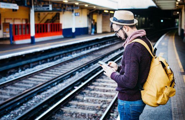 Homem usa celular com chip internacional no exterior em estação de trem
