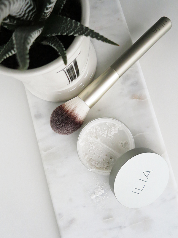 Green organic natural beauty brand ILIA translucent loose powder and cruelty-free face powder makeup brush