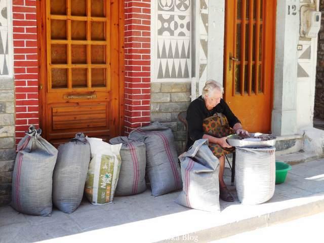 na progu domostwa starsza Greczynka przebiera mastichę, obok stoją pelne wroki mastichy