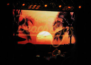 Projected image of a sunset with palm trees, performance by The Beach Boys, Hearst Ranch, San Simeon, California