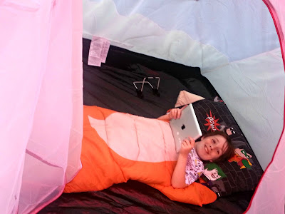 Boy in sleeping bag, inside tent, with ipad