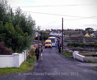 van, bus, car and six pedestrians on a narrow road with stone walls