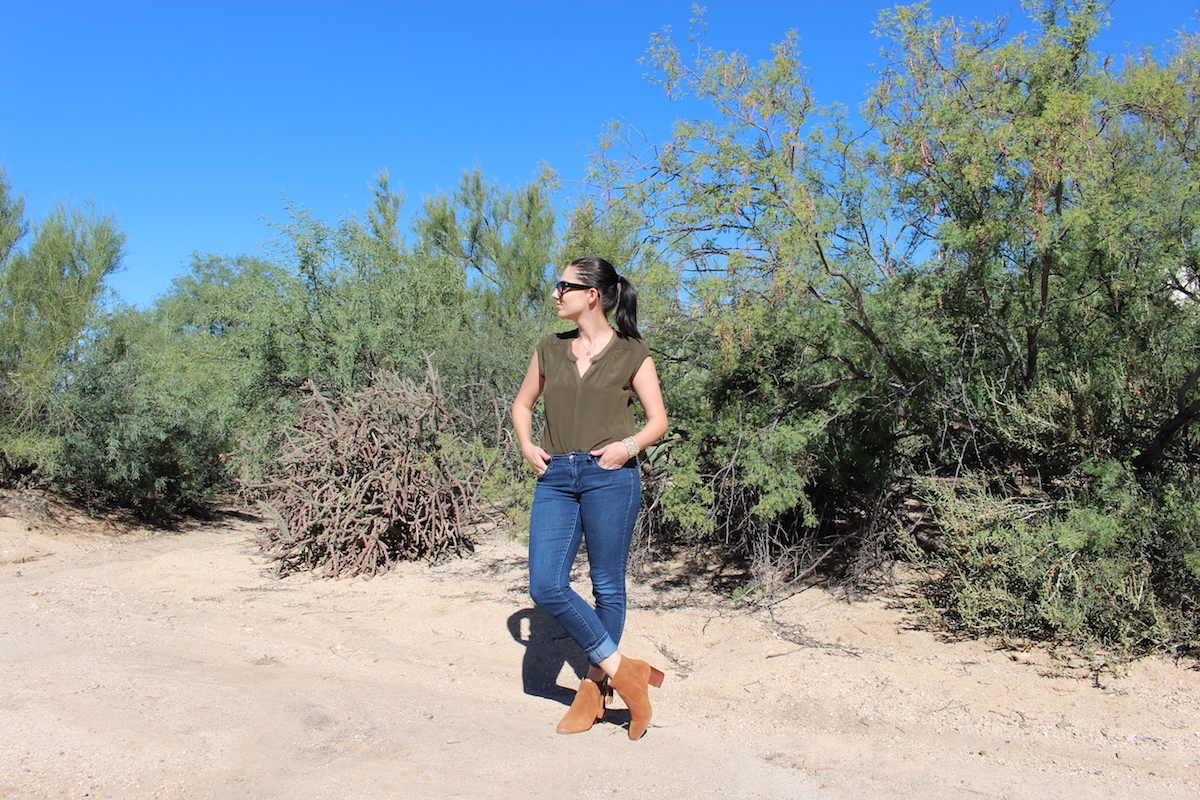 In this photo I'm looking to the right while wearing booties, jeans and a silk blouse, I am standing in the middle of the desert, with crossed legs and looking to the right.