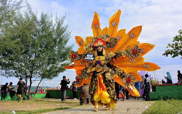 Memotret peserta carnival di jalan menuju gedung serbaguna