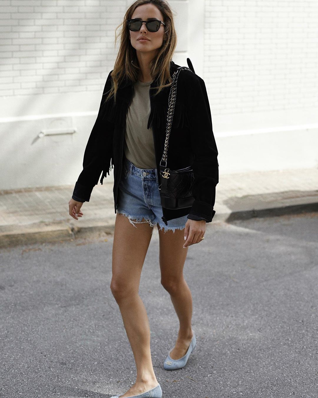 How to Wear Cutoff Shorts for Fall — Alex Rivière in a black jacket, neutral t-shirt, and Chanel bag