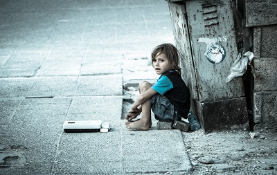 Homeless child crouched in an alleyway.
