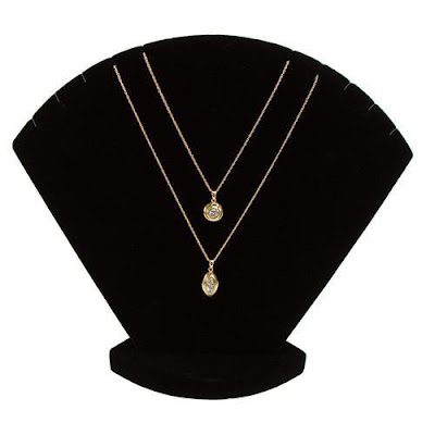 Black velvet displays like the Velvet Necklace Display Stand from Nile Corp are ideal for gold jewelry