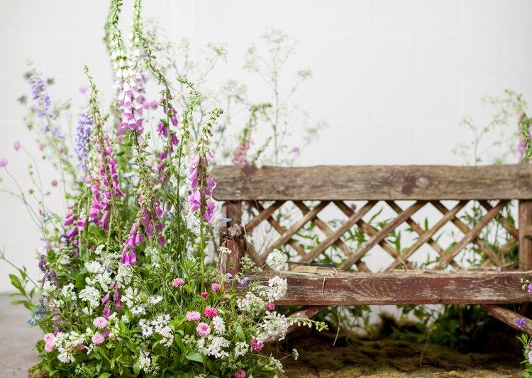 Banco de madera rustico y flores con aire silvestre