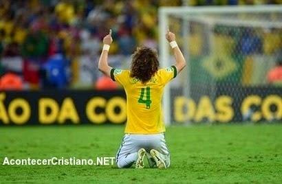 Futbolista David Luiz y orando en el campo
