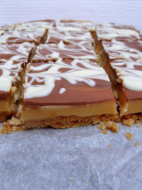 A millionaire's shortbread is a biscuit base covered in chewy caramel and topped with melted milk chocolate. It's also known as homemade Twix bars ! || Le sablé du millionnaire est un biscuit recouvert de caramel et de chocolat au lait fondu. C'est un Twix maison !