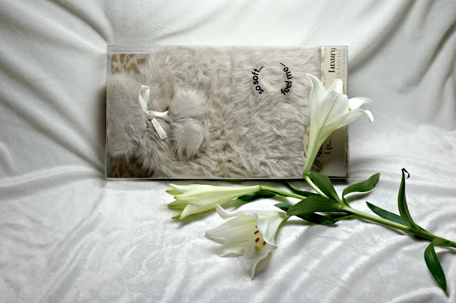 Faux fur hot water bottle in mink, styled with white Oriental Lilies.