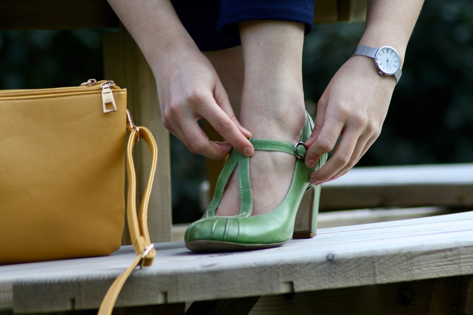 A close up photo of Abbey fixing the buckle on her green shoes, with yellow handbag next to her